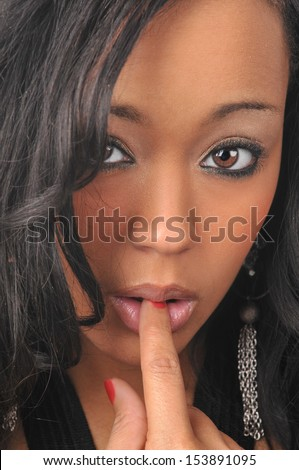 Portrait of young black woman with finger in her mouth