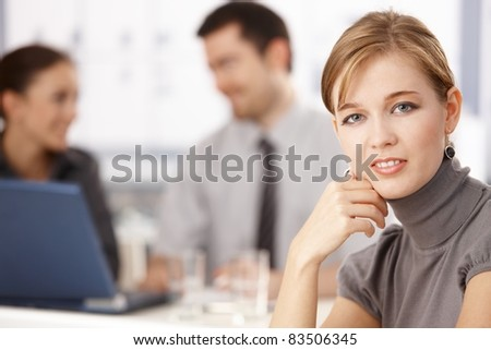 Portrait of young blond businesswoman sitting at table, others chatting behind.? - stock photo