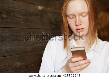 Portrait of young blond Caucasian girl with ivory skin and freckles. Business lady looking down at her smartphone, checking news or chatting in social networks. Office worker sitting in café. - stock photo