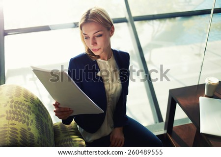 Portrait of young blond hair business woman examining paperwork in bight light office interior sitting next to the window, attractive business woman read some documents before meeting - stock photo