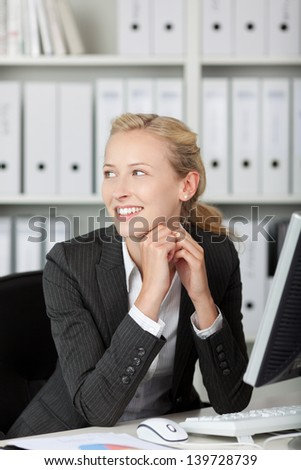 Portrait of young blond smiling businesswoman in her office - stock photo