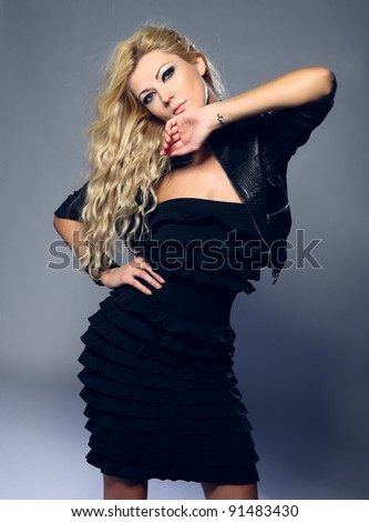portrait of young blond woman in black dress, studio shot - stock photo