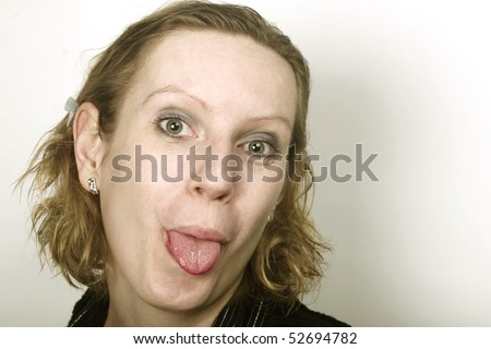 Portrait of young blond woman showing her tongue to camera. Free space on right side. - stock photo