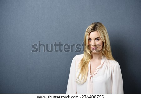 Portrait of Young Blond Woman Wearing Light Colored Blouse Standing Against Blue Grey Background Looking Confident at Camera - stock photo
