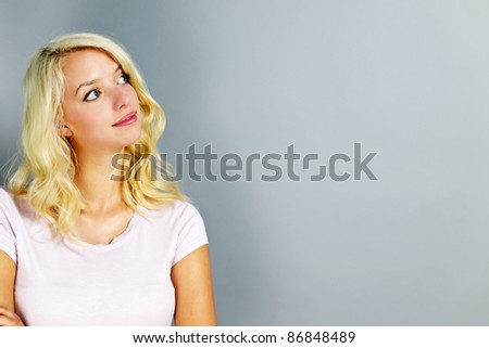 Portrait of young blonde caucasian woman looking to the side and up - stock photo