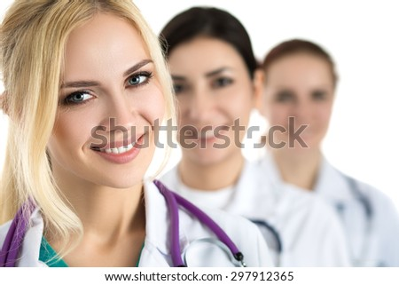 Portrait of young blonde female doctor surrounded by medical team, looking at camera and smiling. Healthcare and medicine concept. - stock photo