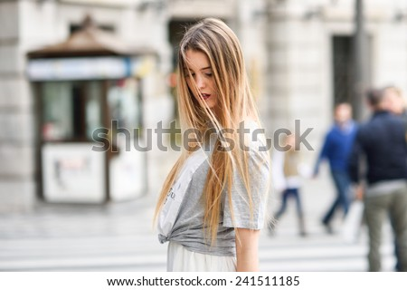 Portrait of young blonde girl wearing casual clothes in urban background - stock photo