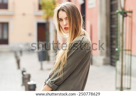 Portrait of young blonde girl wearing casual clothes in urban background