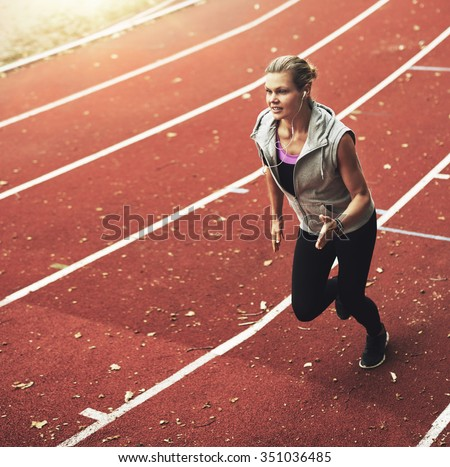 Portrait of young blonde sportswoman running fast on stadium while listening to music