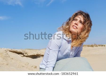 Portrait of young blonde woman on the beach against a blue sky - stock photo