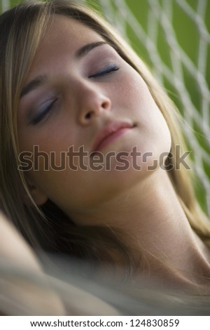 Portrait of young blonde woman sleeping in hammock outdoors - stock photo