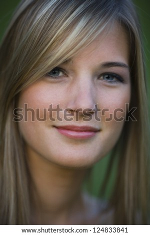 Portrait of young blonde woman smiling outdoors - stock photo
