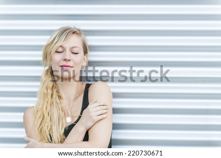 Portrait of young blonde woman with eyes closed against metal background and copy space