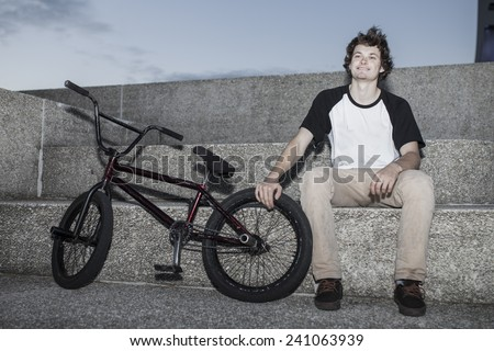 Portrait of young bmx rider in autumn sitting with his bike - stock photo