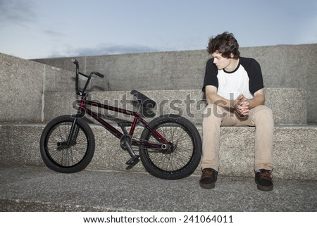 Portrait of young bmx rider in autumn sitting with his bike