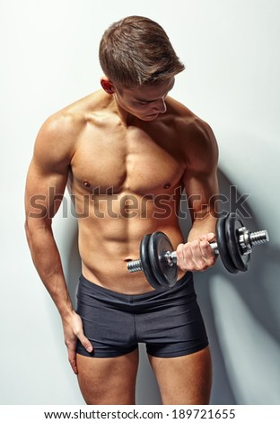 Portrait of young bodybuilder man exercising with dumbbell for training his biceps against white wall - stock photo