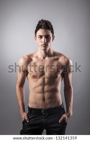 Portrait of young bodybuilder man on a black background - stock photo
