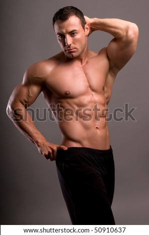 Portrait of young bodybuilder man on grey background. - stock photo
