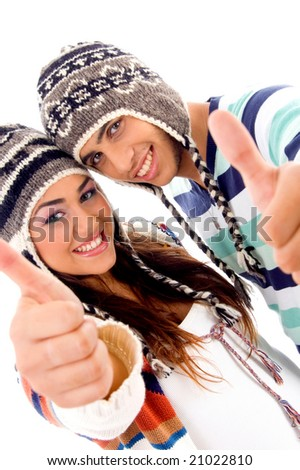 portrait of young boy and girl covering their heads with woolen cap on an isolated white background - stock photo