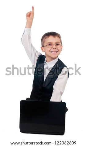 Portrait of young boy dressed up in suit sitting on the floor and working with laptop, isolated on white background - stock photo