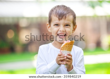 Portrait of young boy eating ice cream outdoors - stock photo
