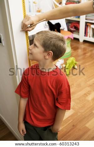 Portrait of young boy getting height measurement in doorway - stock photo