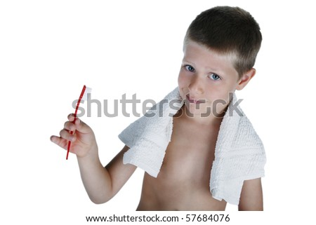 Portrait of young boy holding toothbrush looking at camera with skeptical expression, studio shot isolated on white - stock photo