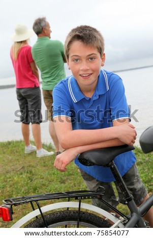 Portrait of young boy leaning on bicycle - stock photo