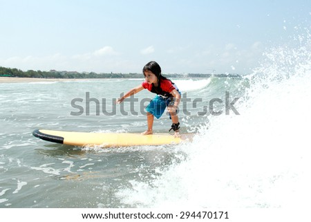 portrait of young boy learn to surf at ocean with splashing water - stock photo