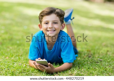 Portrait of young boy lying on grass and using mobile phone in park - stock photo