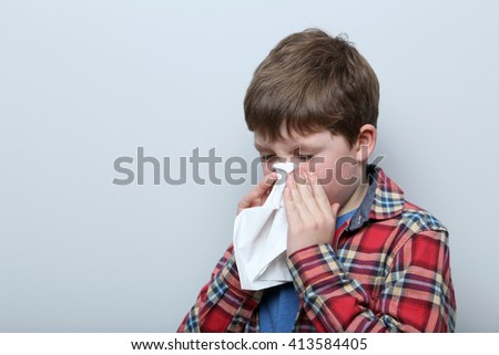 Portrait of young boy on grey background - stock photo