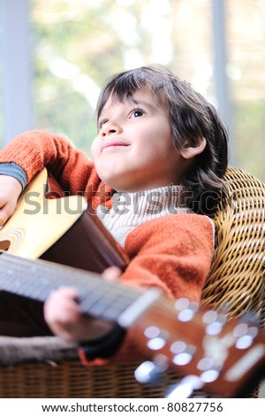 Portrait of young boy playing acoustic guitar at home, closeup - stock photo