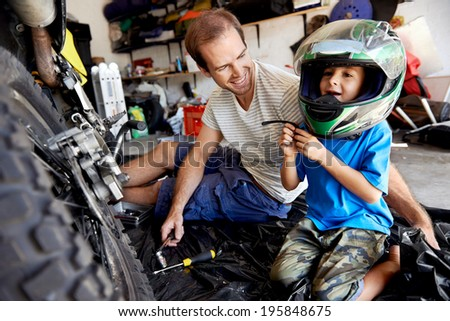 portrait of young boy playing with fathers motorbike helmet and helping his dad with fixing a motorcycle in the garage - stock photo