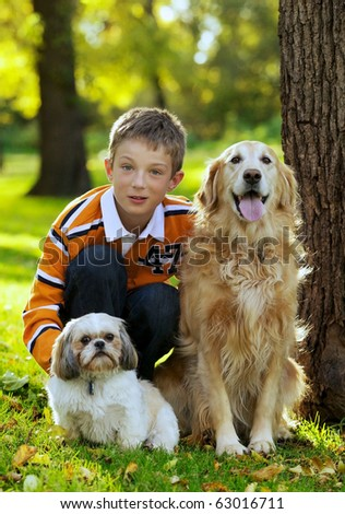 Portrait of young boy posing with his two dogs - stock photo