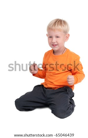 Portrait of young boy sitting isolated on white background - stock photo