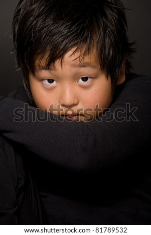 portrait of young boy sitting on a  chair  against black background