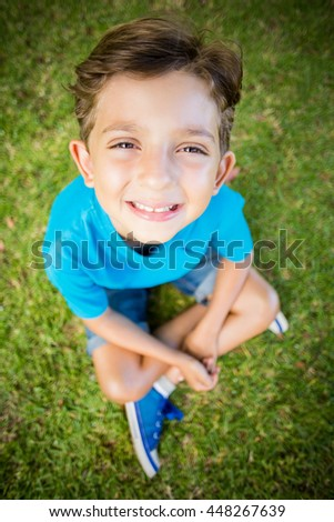 Portrait of young boy sitting on grass and smiling at camera in park - stock photo