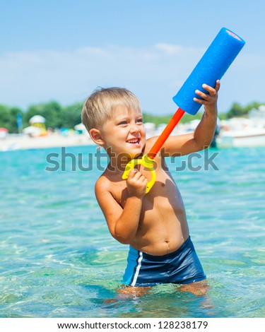 Portrait of young boy swimming and plaing water pistol in the transparent sea