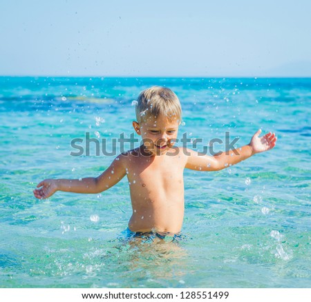 Portrait of young boy swimming and squirting in the transparent sea - stock photo
