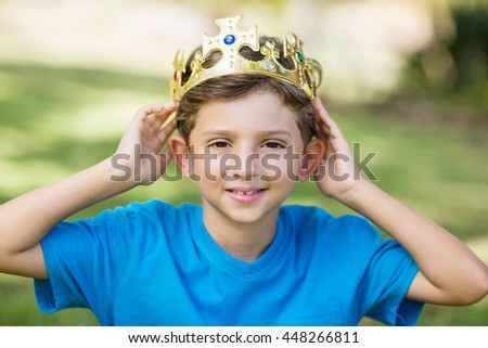 Portrait of young boy wearing a crown in park - stock photo