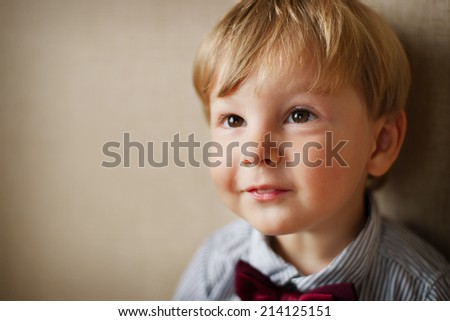 Portrait of Young Boy Wearing Bow Tie Against Plain Wall with Copyspace - stock photo