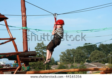 Portrait of young boy wearing helmet and climbing. Child in a wooden abstacle course in adventure playground - stock photo