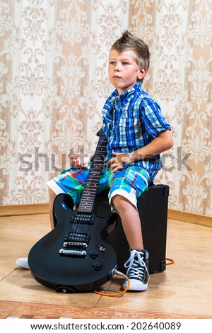 portrait of young boy with a guitar - stock photo