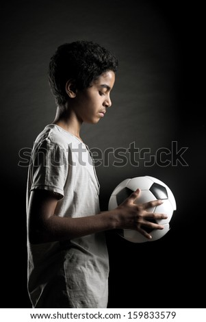 Portrait of young boy with a soccer ball - stock photo