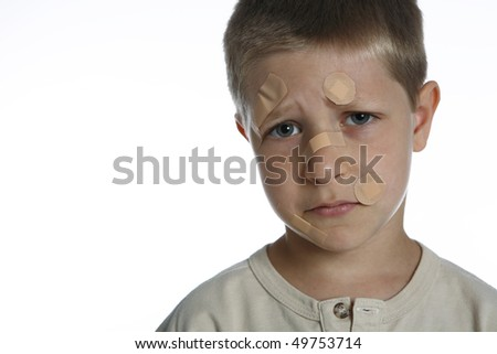Portrait of young boy with band aids on face, studio shot isolated on white background - stock photo