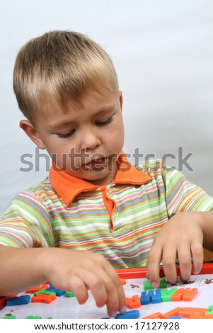 portrait of young boy with magnet letters - stock photo