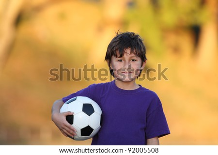 Portrait of young boy with soccer ball at sunset with beautiful blurred gold fall foliage background and copy space to left
