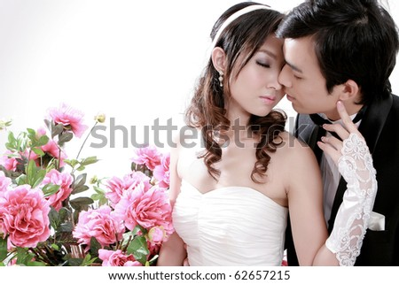 Portrait of young bride and groom kissing each other with sweet floral backgroung - stock photo