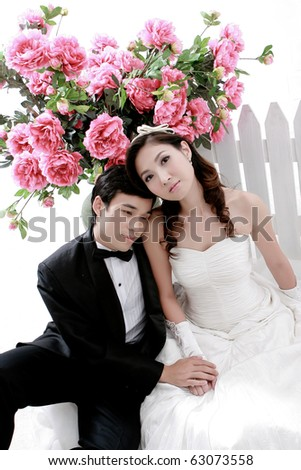 Portrait of young bride and groom sitting together with flower background - stock photo