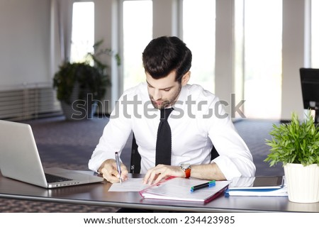 Portrait of young broker doing financial calculations while sitting at office.  - stock photo